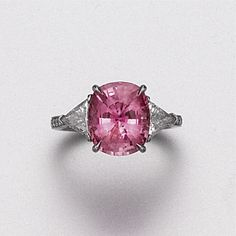 PINK SAPPHIRE AND DIAMOND RING. The cushion-shaped pink sapphire weighing 5.35 carats, flanked by 2 triangular-shaped diamonds weighing approximately .65 carat, the band accented with small round diamonds, mounted in platinum