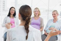 Happy pregnant women listening to gesturing doctor at antenatal class at the hospital - stock photo