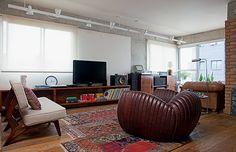 Na foto acima, o sofá, da Desmobilia, fica perpendicular ao rack, revestido de lâminas de ipê, desenhado por Gustavo Calazans e executado pela marcenaria Spada. No teto, trilhos com spots, da Reka. À dir., o móvel que abriga o aparelho de som foi comprado na loja 5 Décadas (Foto: Lufe Gomes)