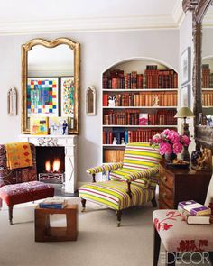 In the library, the armchair is by George Smith, and the mirror above the limestone mantel is 18th-century French; the small canvas artworks are by Anna Raymond, and the collages reflected in the mirror are by Joe Tilson.   - ELLEDecor.com
