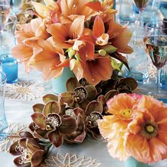 Coral-hued amaryllis and poppies with chocolate cymbidium orchids accented with bright blue elements: silk-wrapped vases and aqua votives.