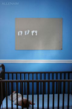 to create nursery art by stamping your baby's footprints to painted plywood or canvas each month for their first year