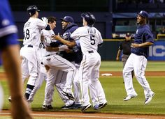 Rays players converge on catcher Jose Lobaton, second from left, after his ninth-inning triple delivers another walkoff victory. Lobaton got a gatorade bath, a whipped-cream pie in the face &  from Matt Joyce ice cream! Rays beat Blue Jays 5-4. (8-16-13) The Rays are now within 1 game of the 1st place Red Sox.