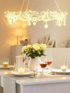 Una guirnalda de luces ( IKEA )  sobre la mesa, de la que caen unos sencillosadornos  navideños puede ser una original y asequible alter...