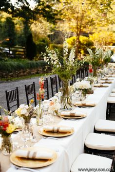 Outdoor wedding reception table settings in orange and yellow