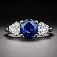 Un rico, zafiro redondo facetado real-azul, con un peso de quilates de dos y medio, irradia entre un par de diamantes de un billón de corte brillantes blancos y espumosos (con un peso 0,85 quilates en total) en este clásico anillo de tres piedras, mano -fabricated en platino. Un magnífico 'mano derecha' o colorido anillo de compromiso alternativa. El vástago del anillo filo liso es actualmente el tamaño 7.