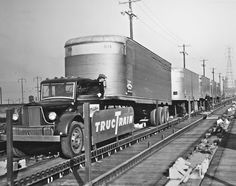 Old trucks being loaded onto railroad cars.  First long haul movement of this type.