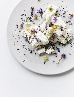 Homemade fresh cheese with flowers and black salt. /
