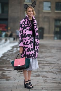 Rosie outlook! Cool coat-jacket in pink with featuring black oversized handwriting, grey textured knee length skirt, olive handbag with pink front section, black strapped sandals. Could loose the bunny ears, though!