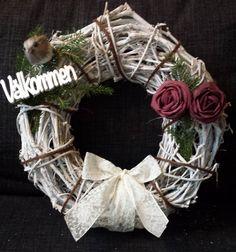 """Krans i vit pil att hänga på dörren. Dekorerad med band, rosor och fågel samt en stick där det står """"välkommen""""."""