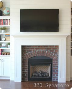 Wood plank wall around fireplace, but with lighter faded brick and the built up hearth