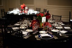Reception seating - Black tablecloth, dark blue and white dinner plates, and red and green floral centerpiece - wedding photo by Michael Norwood Photography