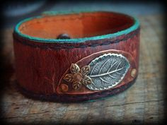 Hand Painted Recycled Leather Belt Cuff Bracelet with Silver Leaf and Brass Flower. $28.00, via Etsy.  SOLD!