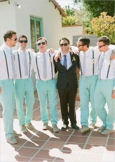 Turquoise pants, white button down shirts paired with light grey ties and black suspenders, matching grey boat shoes and wooden California boutonnieres. Wedding style: retro, beach; Wedding colors: turquoise, peach and white. Photo by Paul Von Rieter, check out more here.
