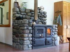 .They made this cast iron stove into a masonry heater. Love this~