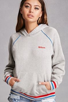 """This repurposed, vintage heathered knit hoodie by Wilson™ features a contrast interior hood, long raglan sleeves with contrast piping, a front kangaroo pocket, an embroidered """"Wilson"""" chest graphic, fleece lining, and striped ribbed trim."""