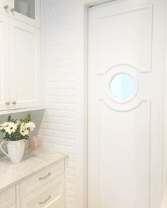 Swinging Door With Moulding And Window. Subway Tile. Marble Countertops.  White Kitchen.