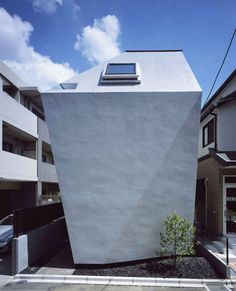 The BB Residence - an irregularly shaped house designed by Yo Yamagata Architects;  massive walls close the house on the side facing the street, while small window piercings open it up towards an inner garden;  a roof terrace makes up for the lack of outdoor space