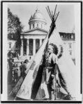 [Mohawk Chief Poking Fire standing before his tipi in front of the State House at Montpelier, Vt.] 1953