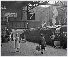 Standing at the head of a Wolverhampton - Paddington train in Birmingham Snow Hill is D1008 Western Harrier.  Platform 7 has all the period charm of the station in 1962, the finger board pointing to the train with the destinations sign-written on it. Passengers were either waiting or boarding, all dressed smartly in comparison with today's fashion, two  schoolboys gaze at the Western and no doubt are impressed by the sound of the twin Maybach engines. Behind the Western a steam freight tr...