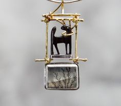 Carolyn Morris Bach: pin/pendant of 18k, sterling, ebony, and dendritic quartz (US $1,400)