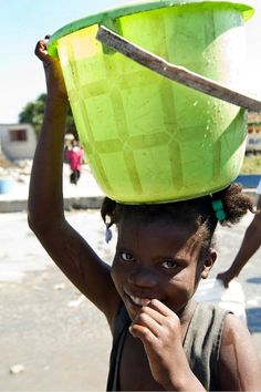 A girl in the shanty town of Cité Soleil, Haiti, near Port-au-Prince, smiles after having struggled for a bucket of water. Cité Soileil, like the Haitian capital, has seen its water resources severely diminished in the aftermath of a powerful earthquake that struck the area on 12 January 2010. (15 January 2010, UN Photo/Logan Abassi)