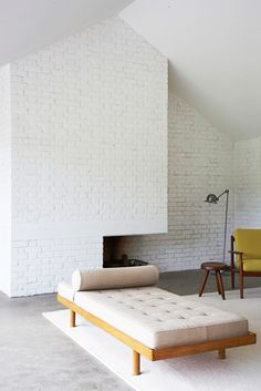white brick wall with fireplace and white daybed / sfgirlbybay