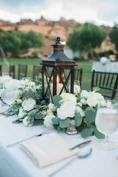lantern centerpiece with greenery and white flowers