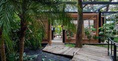 Na parceria entre o arquiteto David Bastos e o paisagista Gilberto Elkis, o bosque arborizado conversa com a arquitetura graças ao caminho de tábuas de madeira, que foi traçado respeitando o espaço entre uma planta e outra, e o sistema de fechamento da casa por brises, que permitem a relação interior/ exterior. O projeto fez parte da edição 2015 da Casa Cor São Paulo