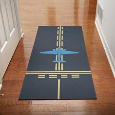 You're ready for takeout with our Taxiway Hallway Runner Mat. An airplane silhouette, taxiway and hold short markings are printed on the gray polyester surface. The skid-resistant backing will not curl or crack and the Mat is machine washable and made in Airplane Bedroom, Airplane Decor, Airplane Design, Airplane Silhouette, Aviation Decor, Travel Office, Hallway Runner, Office Interiors, Boy Room