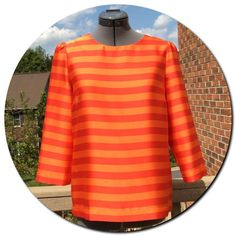 "Vince Camuto True Rose/Warm Orange Striped Top Vince Camuto True Rose/Warm Orange Striped Top. Striking blouse with exposed gold zipper in the back. 3/4 length sleeves gather at the top. Fabric: 97% Polyester and 3% Spandex. Measurements: Bust 19"" and Length 23"". Size 6. Gently worn. Vince Camuto Tops Blouses"