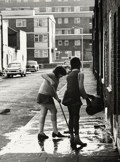 Washing the doorstep in Shap St with the Fellows Court Estate beyond, 1974. (Copyright Hackney Archives Department)