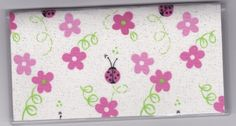 "Ladybug and Pink Flowers on Glitter White Checkbook Cover by Tickled Pink Boutique. $5.00. The sturdy clear VINYL COVER encases a fabric bonded design. Measuring 6 1/4"" x 3 1/4"",  the cover fits all standard bank checkbooks and banking registers.  All checkbook covers come with a register flap and a duplicate check flap  just like the bank, only flashier.  These checkbook covers are a great alternative to the expensive covers offered by banks and online check companies."