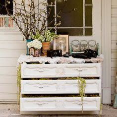 Shabby Chic. An old dresser can make a unique stand for anything from engagement pictures and party favors to a wedding cake. Open the drawers and stuff them to overflowing with bright seasonal flowers
