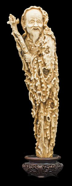 CHINESE CARVED IVORY FIGUREOf a bearded Luohan, standing wearing a long 'wood textured' hooded tunic, holding a staff in his left hand, and a lingzi root in his right. Mounted on a carved wood stand. Overall Height 11 5/8 in. Weight 1020.7 g. Provenance: Bonhams, November 10, 2003, lot 239.