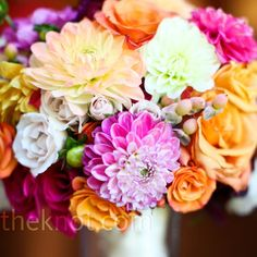 A mix of orange and pink roses and dahlias accented with hypericum berries had a bright, summery look.