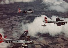 P-51 Mustangs provide cover to a formation of B-17G Flying Fortresses. It's late enough in the war so the factory was no longer required to paint the wings or fuselage as aerial camouflage.