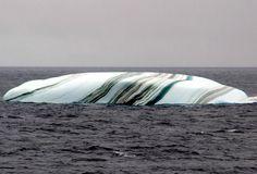 Un iceberg multicolore au milieu de la mer.