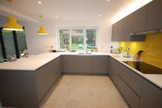 Fusion Linear kitchen in Dust Grey with Mistral Polaris worktops and bright yellow glass splashback. by Saffron Interiors 01483 Grey Kitchen Designs, Kitchen Room Design, Interior Design Kitchen, Kitchen Decor, Grey Yellow Kitchen, Charcoal Kitchen, Bathroom Yellow, Kitchens And Bedrooms, Grey Kitchens