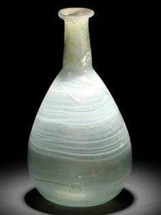 A Roman pale blue marbled glass flask  Circa 1st Century A.D. Of piriform shape with slender neck, decorated with swirling bands of opaque white, 5¾in (14.5cm) high