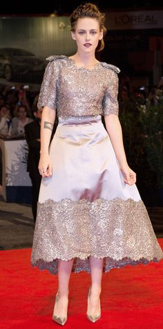 "Kristen Stewart wowed at the premiere of ""Equals"" at the Venice Film Festival in a Chanel Haute Couture gray lace and silk embroidered number with a high-low hem. Stewart gave the intricate dress an edgy spin by swiping on a vampy red lip and accessorizing with high-shine pointy-toe pumps."