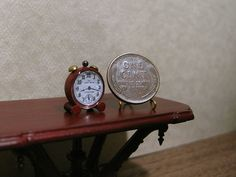 """Tiny red alarm clock that stands just 5/8"""" tall. She used a clear cabochon sticker to simulate glass. More clocks along with how they were made on the  blog link."""