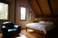 Bedroom in mudbrick home. Like the brick walls rendered white with the exposed timbers