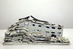 """Alison Ruttan's """"Natural Disaster"""", is a series of ceramic sculptures basedon an ever-expanding archive of imagesof destroyed buildingsfound on the web. While much of this work may look similar to the effects of natural disasters it is important to remember that these are not accidents of nature but entirely man made acts of destruction."""
