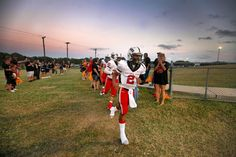The Victoria East Titans run onto the field through a cheering crowd of parents and supporters at the East v. West rivalry game at Memorial Stadium. Victoria West, Photos Of The Week, Crowd, Parents, Memories, Running, Game, Dads, Memoirs