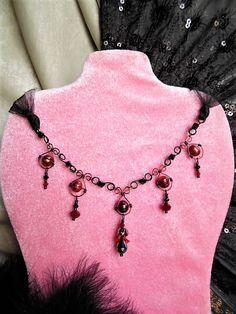 Exquisitely Dark, Romantic Victorian Goth, Red and Black Choker! Appropriate for any Goth Queen! Made with 10x8mm Rusty Red pearls, Black Crystals, Red opaque and clear red crystals, a gunmetal crystal drop in the center of the choker, topped with a red lucite lily, gunmetal bead cap, and an opaque red crystal. Black glass seed beads are used as spacers. Handmade red and black enameled copper wire work links to create the chain and drops, and finished with black shimmer tulle ties, making…
