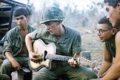 Soldiers gather round a guitar player and sing songs on Jan. 18, 1968