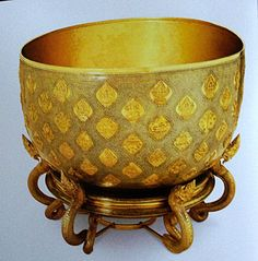 Gold nielloware bowl with the 108 auspicious symbol. The bowl is placed on top of a circular platform that is held aloft by mythical Nagas or  Serpents.    Production 2 years by 28 artisans Diameter. 108 cm. Height.  61cm Base height.  44 cm.
