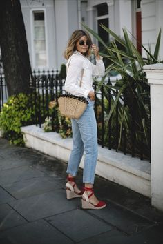 Emma Hill wears cream broderie anglais blouse, Paige bleach wash high waisted jeans, straw basket bag with pom poms, red canvas wedge espadrilles, gold Ray Ban round metal sunglasses, spring outfit