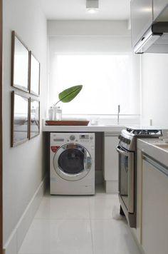 Pequenina, a bancada da lavanderia fica junto à janela e segue a mesma decoração da cozinha: os armários são iguais e a bandeja organizadora é de madeira, assim como as molduras.